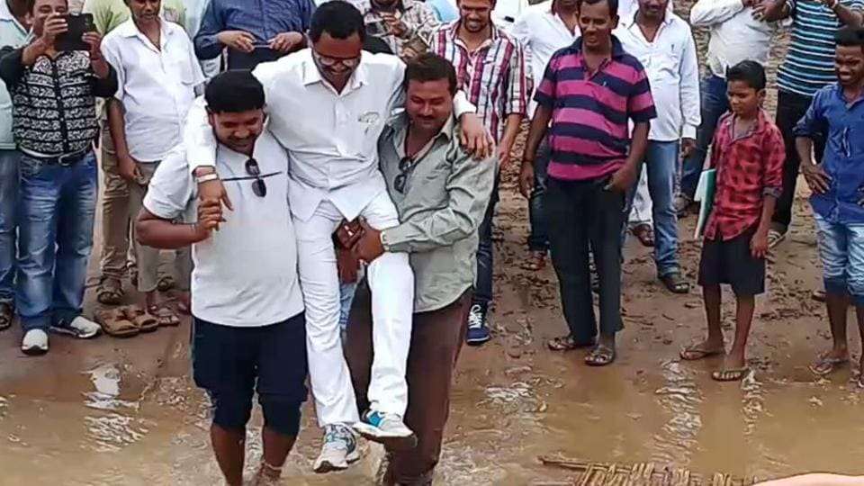 Odisha MLAwas lifted by his supporters to cross a muddy stretch.
