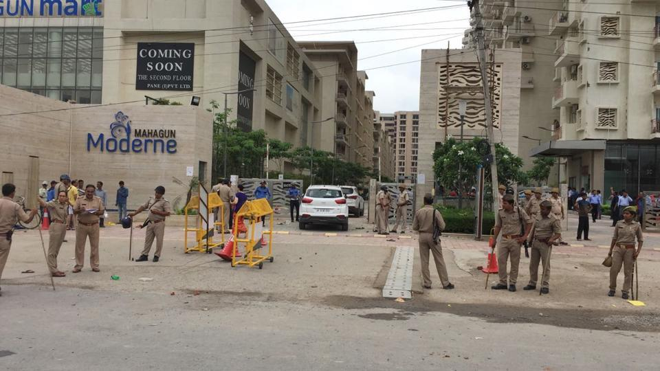 Policemen stand guard outside a housing society, Mahagun Moderne in Noida Sector 78 on Wednesday after a mob attacked the society.