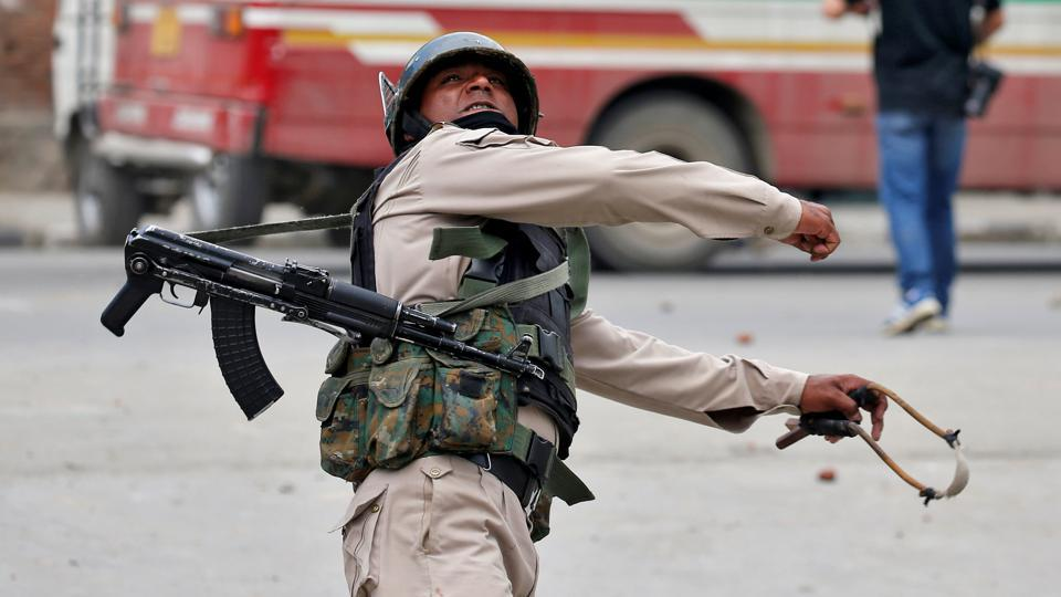 In retaliation a  police officer throws a rock at stone pelters during disturbances in Srinagar. 'Pellet guns are intended not to be lethal, but their use by India's security forces has caused severe injuries and several deaths of bystanders, women and children among them,' said one 25-year-old officer. (Cathal McNaughton / Reuters)