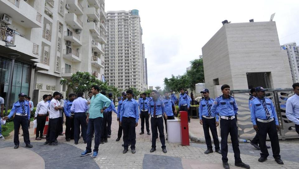 Security guards stand guard outside a housing society, Mahagun Moderne, in Noida Sector 78 on Wednesday after a mob attacked the society.