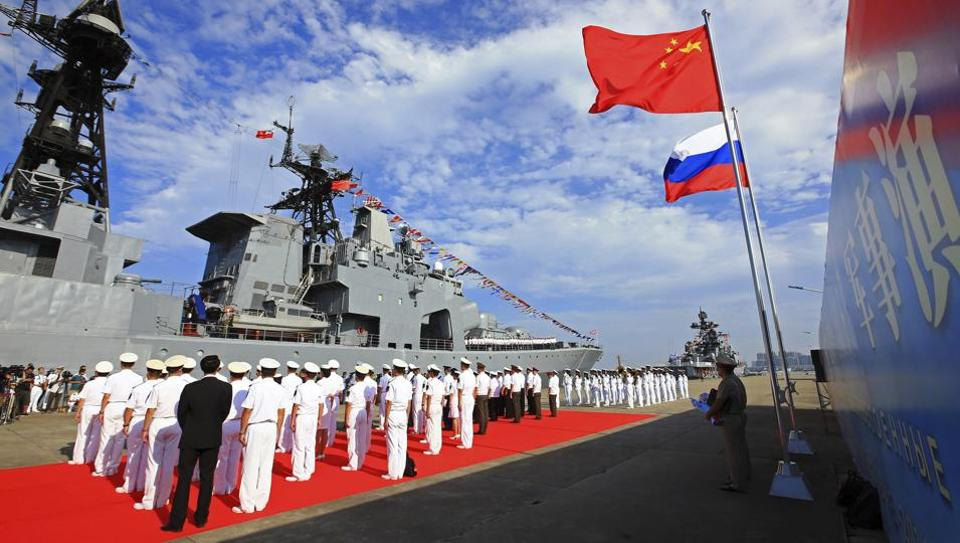 In this September 12, 2016, photo released by China's Xinhua News Agency, officers and sailors of China's People's Liberation Army (PLA) Navy hold a welcome ceremony as a Russian naval ship arrives in port in Zhanjiang in southern China's Guangdong Province.