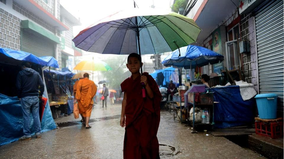 A young Tibetan Buddhist monk cross a street during rain in Mcleodganj near Dharamsala on Wednesday. (Shyam Sharma/HT Photo)