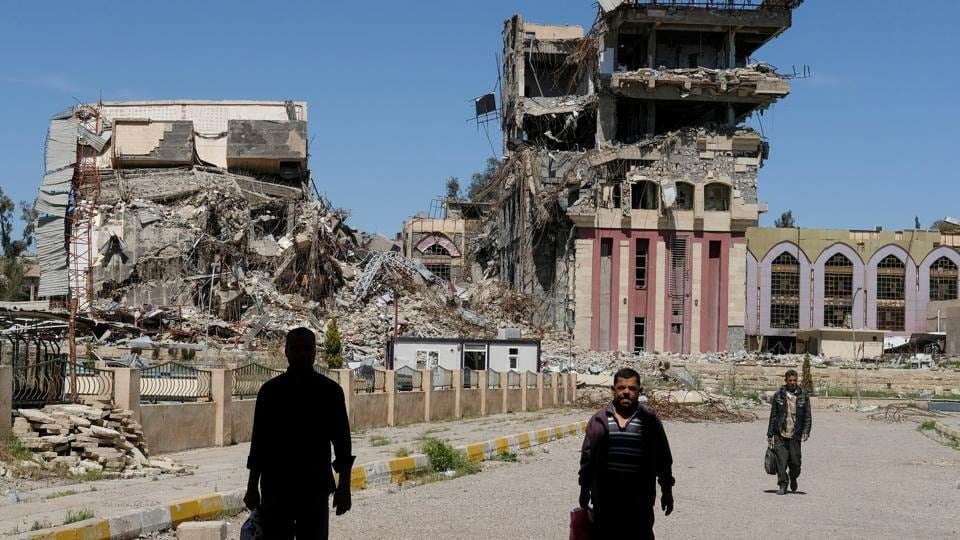 People walk in front of the remains of the University of Mosul, which was burned and destroyed during a battle with Islamic State militants, in Mosul, Iraq.