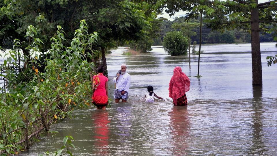 Villagers wade through a flooded street at Kureni Bori in Morigaon district of Assam.