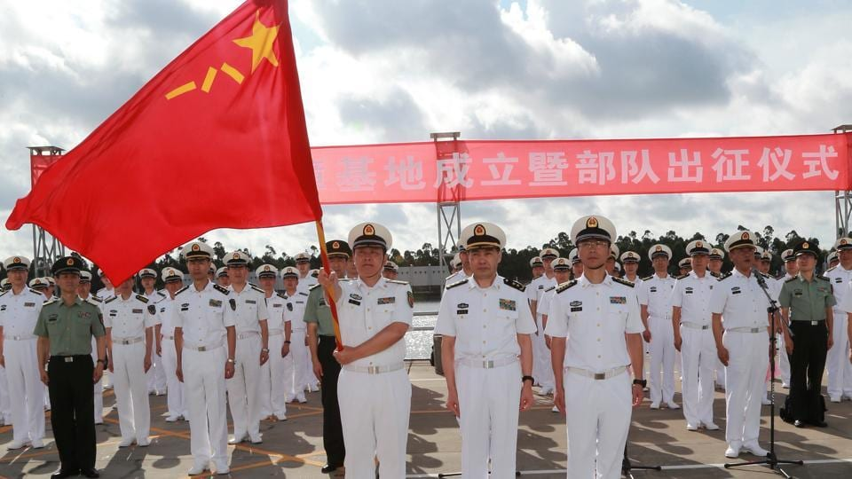 A soldier of China's People's Liberation Army holds a PLA flag as others stand guard at a military port in Zhanjiang, Guangdong province on Tuesday.