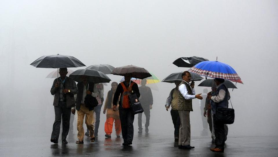 People walking through the dense fog with umbrellas during heavy rainfall at the Ridge, Shimla, on Wednesday. (Deepak Sansta/HT Photo)