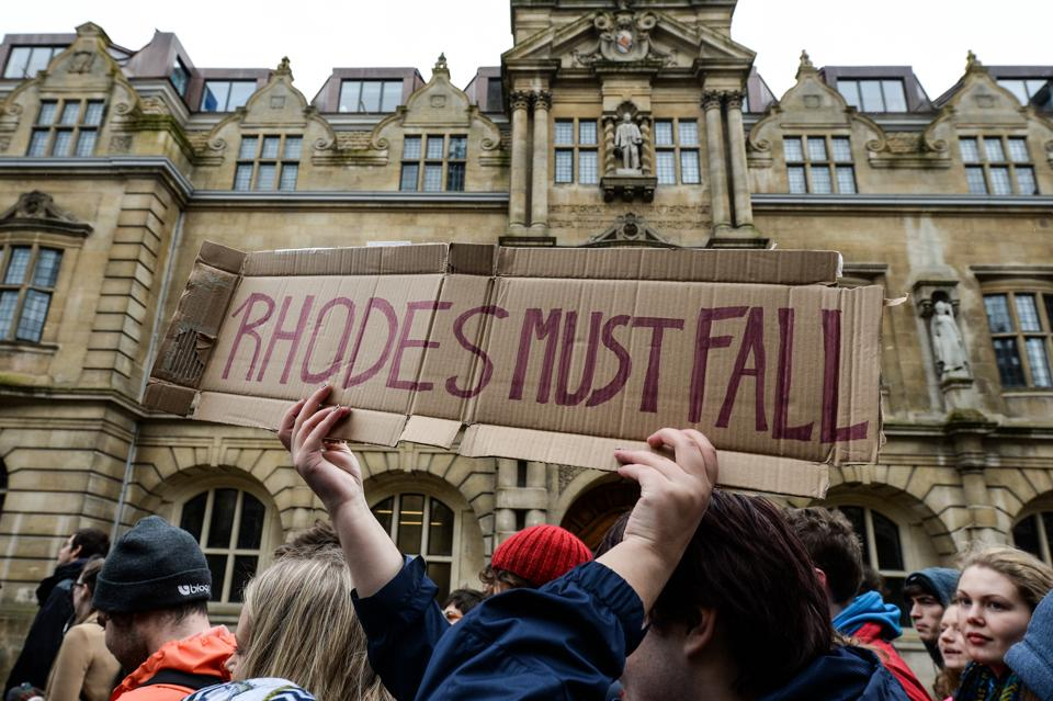 Students march past Oxford University's Oriel College and the statue of Cecil Rhodes. The demonstrators were calling for statues of colonial era figures including Cecil Rhodes and Queen Victoria to removed from university campuses.  Recently Oxford University announced it is tweaking its curriculum to make a paper on non-European history obligatory for history students.