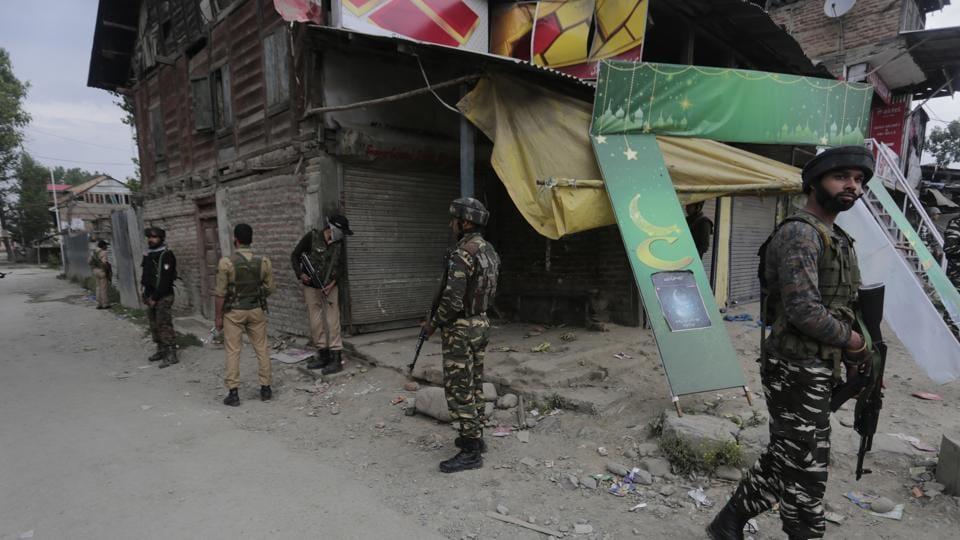 Security force personnel stand guard at the site of the militant attack on pilgrims in Batengo village, Anantnag district, Kashmir.