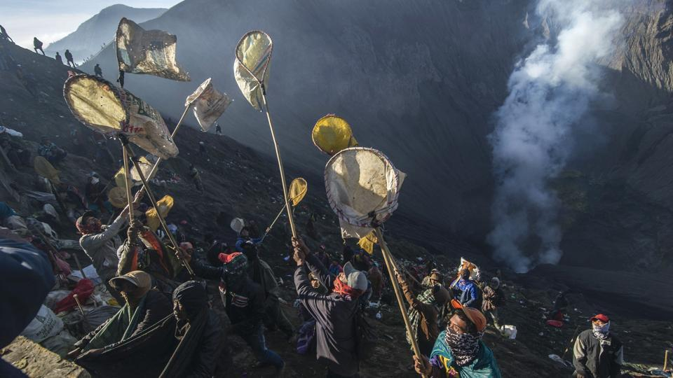 Members of the Tengger tribe who live around mount Bromo-Semeru volcano throw live offerings into the crater to honour Sang Hyang Widhi, and Mahadeva, the God of the mountain. (JUNI KRISWANTO / AFP)