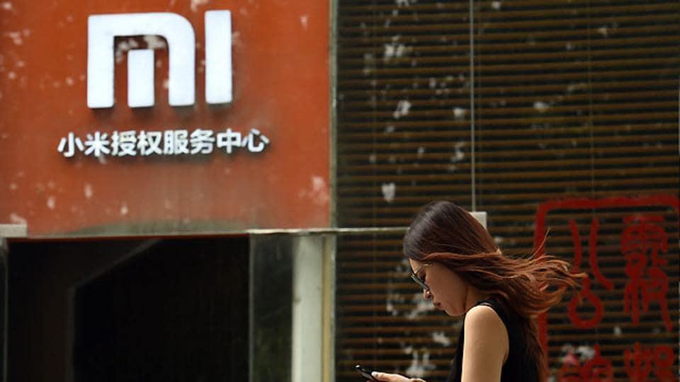 A woman walks past a Xiaomi logo outside a Xiaomi service centre in Beijing.