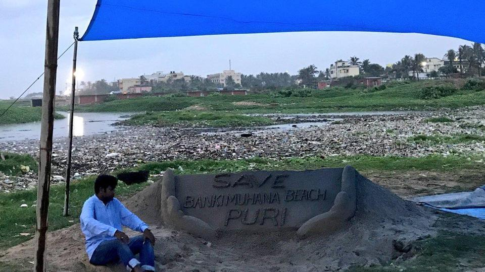 The sand artist Sudarsan Patnaik sitting on a hunger strike to protest against beach pollution at Bankimuhan.