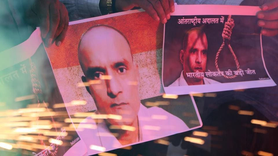 People in Ahmedabad hold posters of Kulbhushan Jadhav as they celebrate the International Court of Justice on order May 18, 2017.