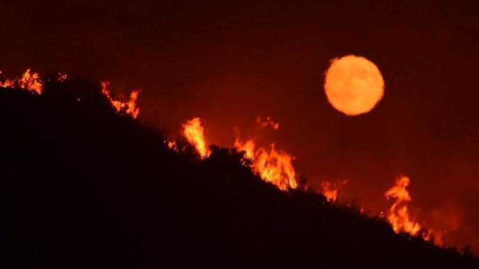 The full moon rises over flames of the Alamo fire on a hilltop off Highway 166 east of Santa Maria, California. (Reuters)