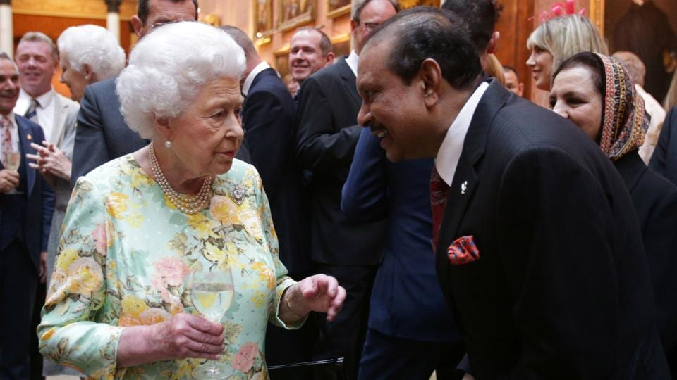 Britain's Queen Elizabeth II  meets Yusuff Ali Musaliam during a reception for the winners of The Queen's Awards for Enterprise 2017 at Buckingham Palace in central London on July 11, 2017.