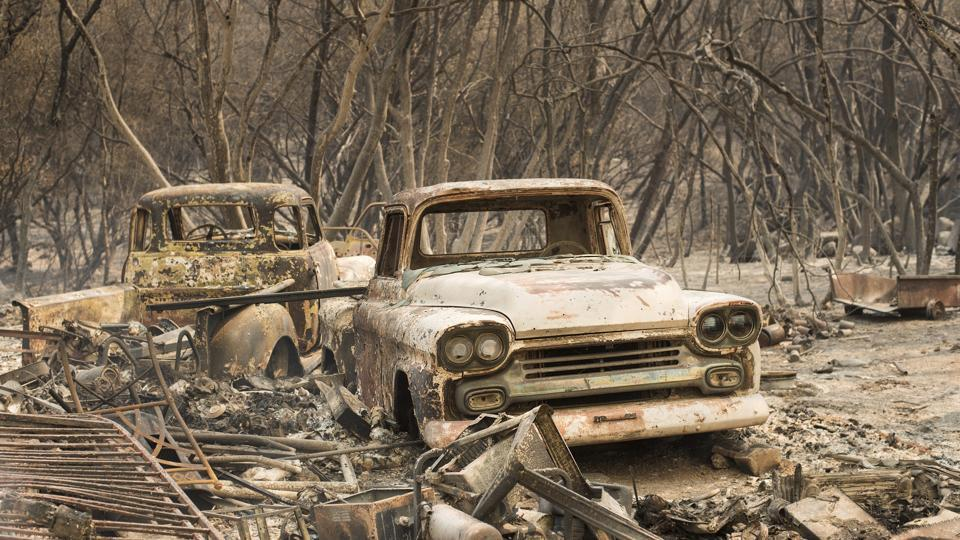 Trucks burned by a wildfire rest in a grove near Oroville, Calif. The fast-moving wildfire in the Sierra Nevada foothills destroyed structures, including homes, and led to several minor injuries, fire officials said. (Noah Berger / AP)