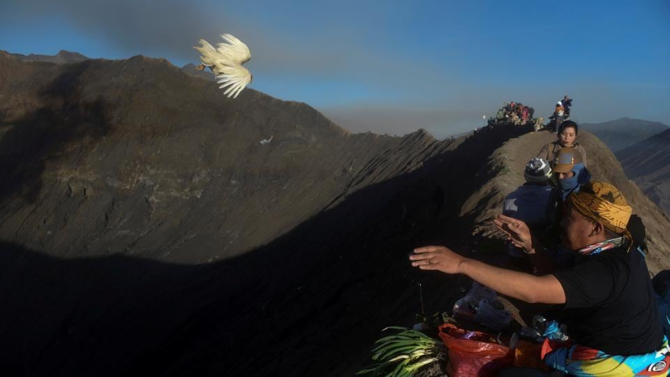 A villager throws a chicken towards the crater of Mount Bromo as an offering during the Kasada ceremony in Probolinggo, Indonesia. (Zabur Karuru / REUTERS)