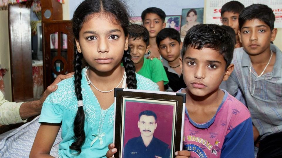 Martyred lance naik Ranjit Singh's children –  Kajol and Kartik – hold up his photograph at their residence in Burn village. Singh and another soldier, Satish Bhagat, fell victim to enemy snipers along the line of control in Kupwara district on Wednesday.