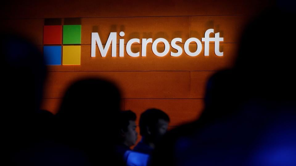 The Microsoft logo is illuminated on a wall during an event in New York City.