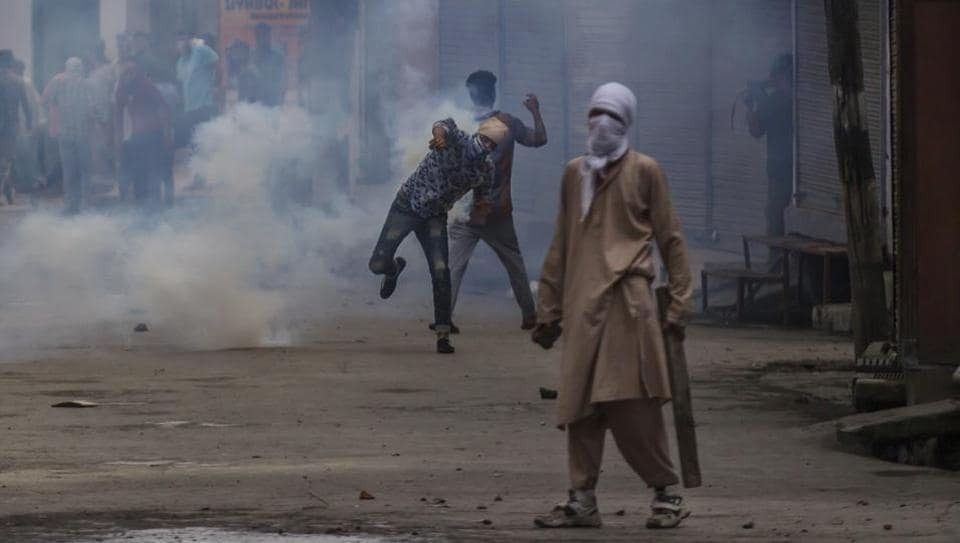 A Kashmiri protester throws back an exploded tear gas shell as they clash with government forces during curfew in Srinagar on Wednesday.