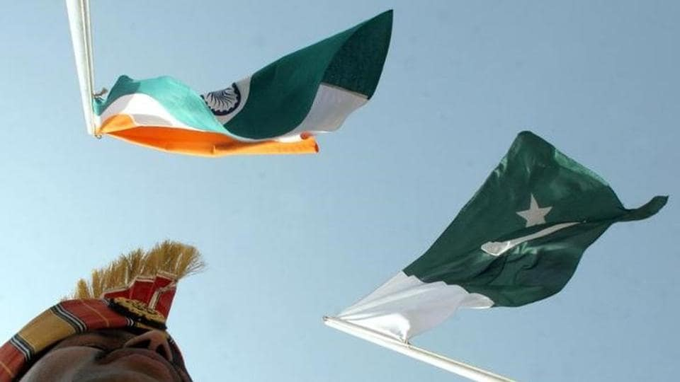 An Indian border guard stands near the India  and Pakistan flags during a fair at Chamliyal in Jammu and Kashmir.