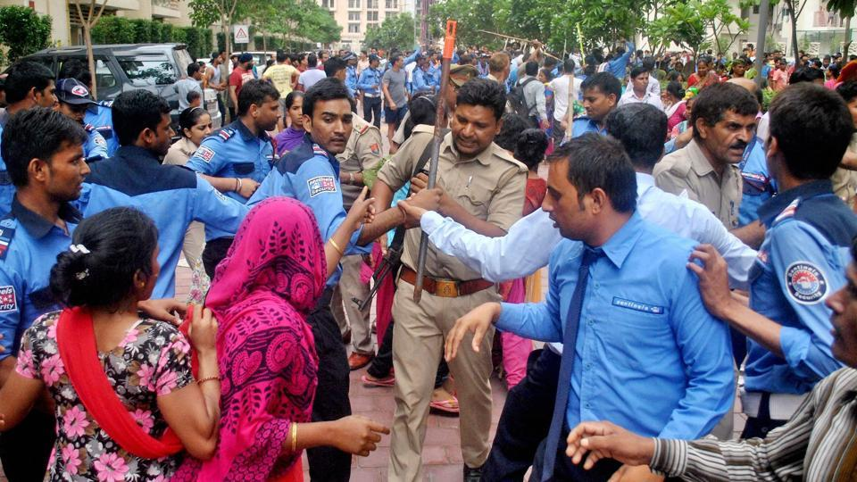 Noida: Police and private security personnel in a clash with the local villagers who gathered at a housing society to protest after a domestic help was allegedly beaten by her employers on suspicion of theft, in Noida on Wednesday.