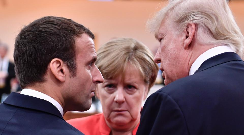 US President Donald Trump (R), French President Emmanuel Macron (L) and German Chancellor Angela Merkel (C) at the start of the first working session of the G20 meeting in Hamburg, Germany, on July 7, 2017.