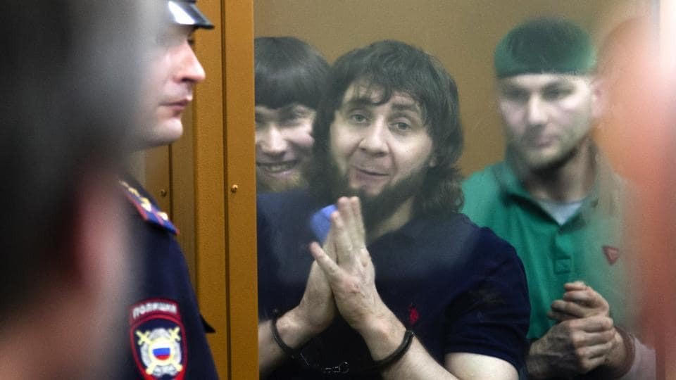 Zaur Dadayev, center left, Anzor Gubashev, center, and Shadid Gubashev, center right, listen to the sentence in a court room in Moscow, Russia, on July 13, 2017.