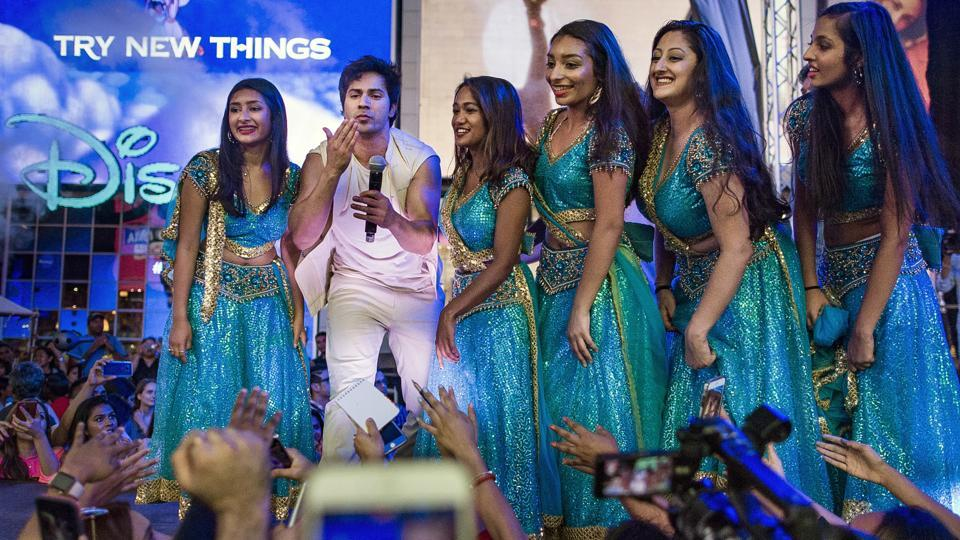 Varun Dhawan greets his fans in between dancers wearing traditional Indian dresses during The 18th edition of the International Indian Film Academy (IIFA) awards weekend event at Times Square on Thursday. (AP)
