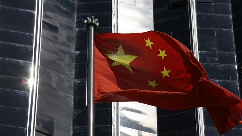 A Chinese flag is hoisted outside a commercial building in Shenzhen, China's southern Guangdong province.