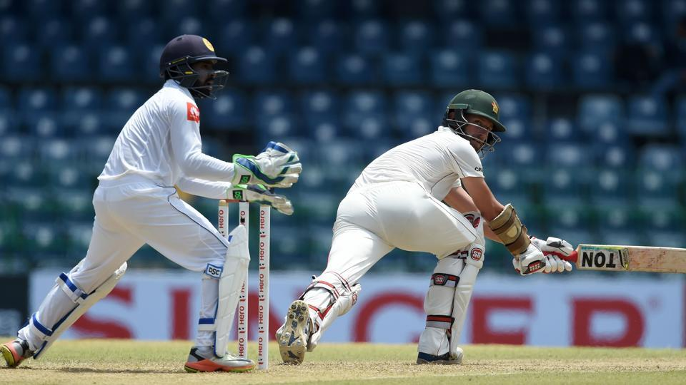 Zimbabwe cricketer Craig Ervine (R) plays a shot as Sri Lankan wicketkeeper Niroshan Dickwella (L) looks on during the first day of the only one-off Test match between Sri Lanka and Zimbabwe at the R Premadasa Cricket Stadium in Colombo on Friday. Get live cricket score of Sri Lanka vs Zimbabwe here.