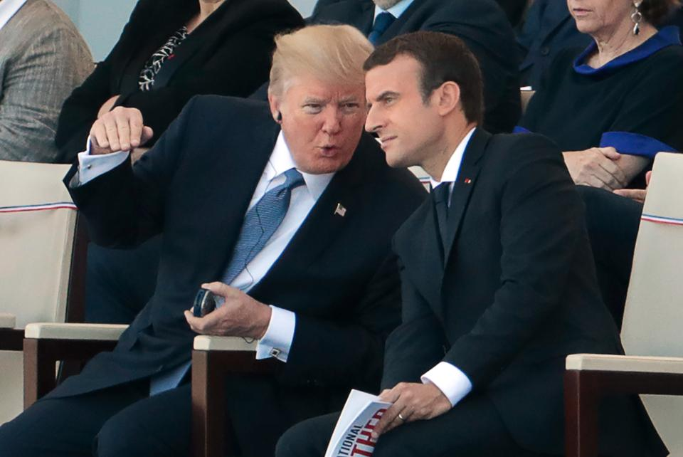 French President Emmanuel Macron listens to US President Donald Trump as they attend the annual Bastille Day military parade on the Champs-Elysees avenue in Paris on July 14, 2017.
