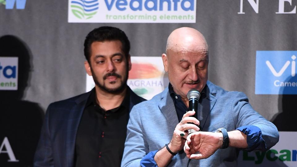 Salman Khan (L) looks on as Anupam Kher checks time during a press conference ahead of the 18th International Indian Film Academy (IIFA) Festival. (AFP)