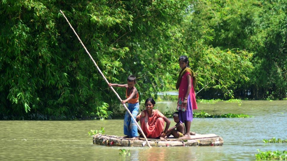 A boy travels with other family members on a homemade raft across flood waters in the Kamrup district of Assam.