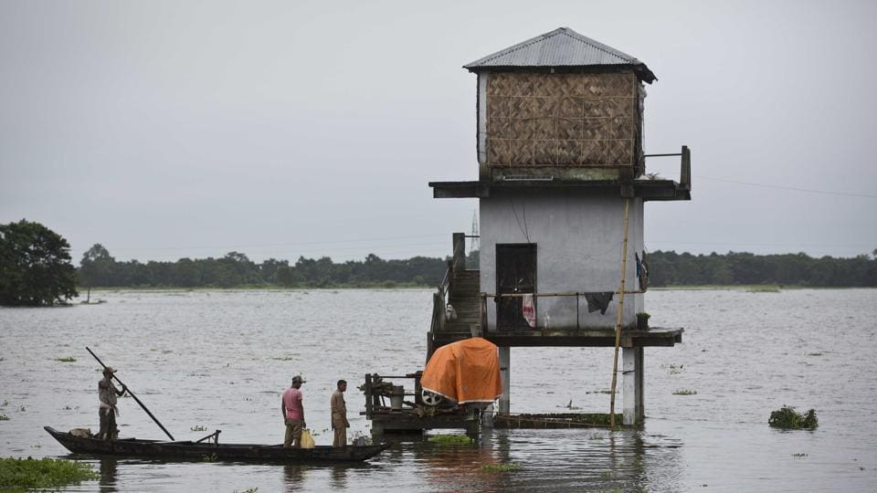 Indian forest officials leave for patrolling from their inundated watch tower in the flooded Kaziranga National Park.  (Anupam Nath / AP)