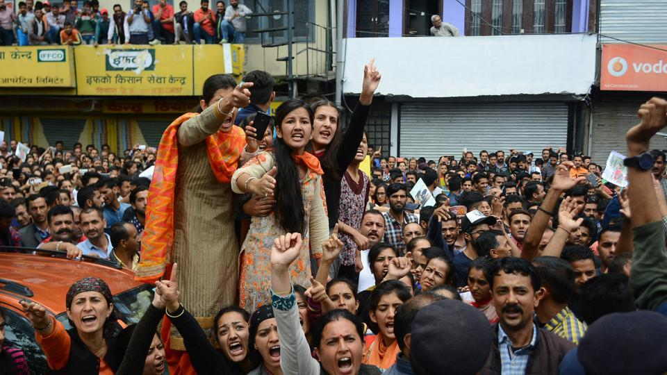 A large crowd blocks road in Shimla in protest against rape and murder.
