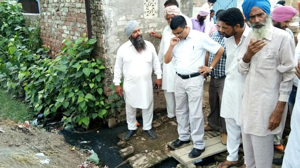 Health officials from Community Health Centre, Sudhar, interacting with residents; and water pipes running through the sewage water, at Saholi village in Sudhar near Ludhiana on Thursday.