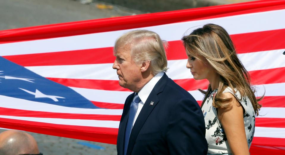 US President Donald Trump and First Lady Melania Trump stand in front of the American flag at the end of the traditional Bastille Day military parade on the Champs-Elysees in Paris on July 14, 2017.