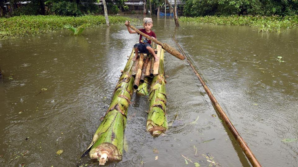 A boy rows a makeshift raft outside his submerged house in the flood-affected Kuthori village near Kaziranga National Park in Nagaon district, in the northeastern state of Assam, India. (Anuwar Hazarika / REUTERS)