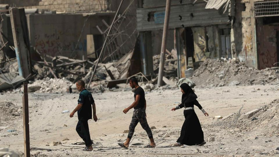 Iraqis walk on a damaged street in west Mosul on July 13, 2017, a few days after the government's announcement of the