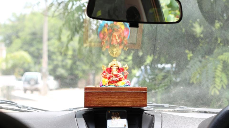 The talking idol of Ganapati sits on a car dashboard, monitoring whether the driver is within speed limit or not.
