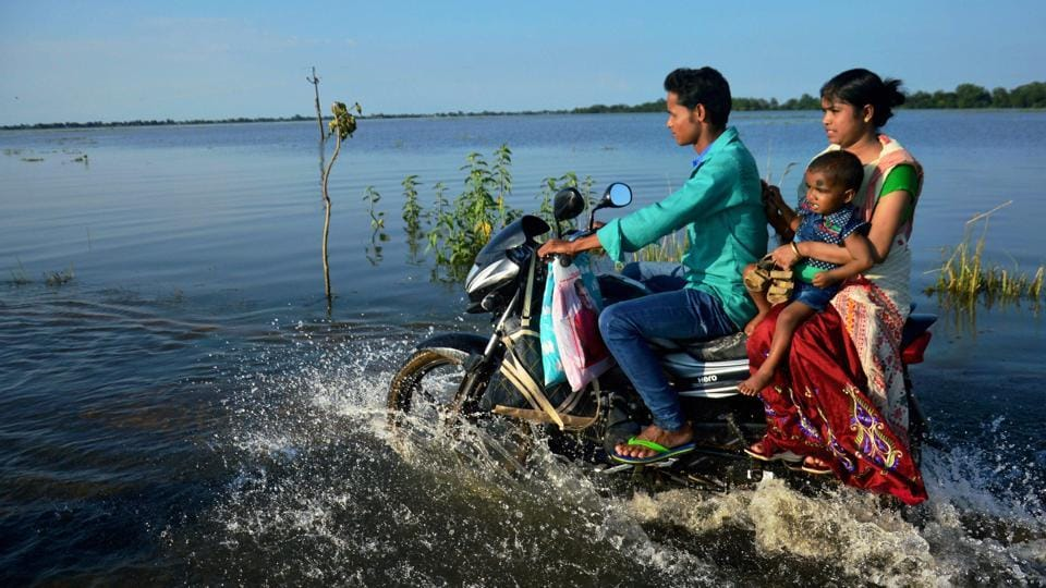 A family travels on bike through a flooded road at Jamlai village in Kamrup district, Assam. The flood situation in the state has turned grave with the 17,43,119 people in 2,450 villages of 26 districts reeling under flood during the past 24 hours. (PTI)