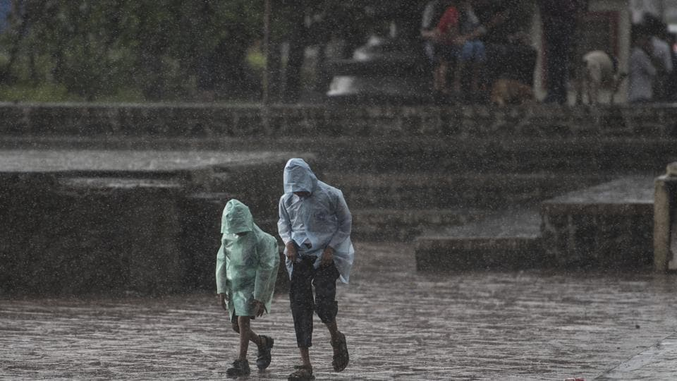 Children bow their heads and brave the rain at Carter Road in Bandra on Friday.
