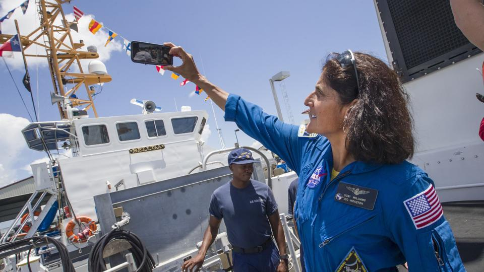 NASA astronaut Sunita Williams takes a photograph after boarding the US Coast Guard Cutter Manowar to view a training exercise using a full scale mock-up of the Orion capsule in the Gulf of Mexico off the coast of Galveston, Texas on July 13, 2017.