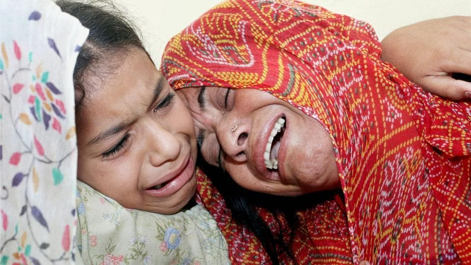 L-R) Daughter Kajol and wife Neha Devi of Lance Naik Ranjit Singh wail at the loss of Singh at their residence in Bhalwal village in Jammu on Thursday. Singh was among the two soldiers killed yesterday as Pakistani troops violated the ceasefire along the Line of Control (LoC) in Kashmir in Kupwara district. (PTI)