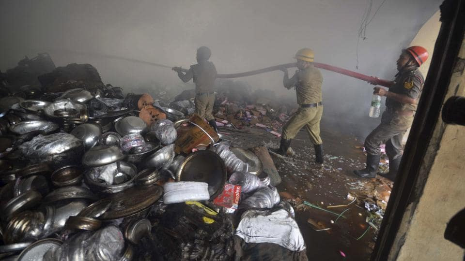 Firefighters extinguish fire at an electronic warehouse at Badharghat in Agartala. The warehouse caught fire due to a short circuit. (PTI)