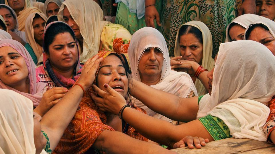 Neha Devi (3L), wife of slain Indian soldier Lance Naik Ranjeet Singh, is consoled by relatives at his home in Burn village, about 28km from Jammu. Two Indian soldiers were killed on July 12 by firing from across the line of control between India and Pakistan in Keran sector of Kupwara district in Kashmir. (AFP)