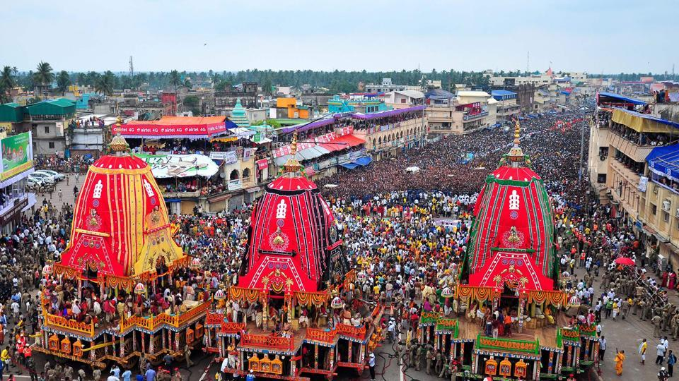 This photo taken on June 25, 2017 shows devotees by huge chariots representing Lord Jagannath, Brother Balabhadra and Devi Subhadras in front of the Shree Jagannath temple to celebrate the Rath Yatra festival in Puri.