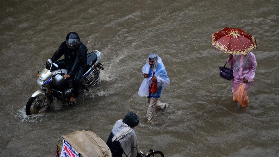 Indian commuters wade along a waterlogged street after heavy rains in Allahabad. (SANJAY KANOJIA / AFP)