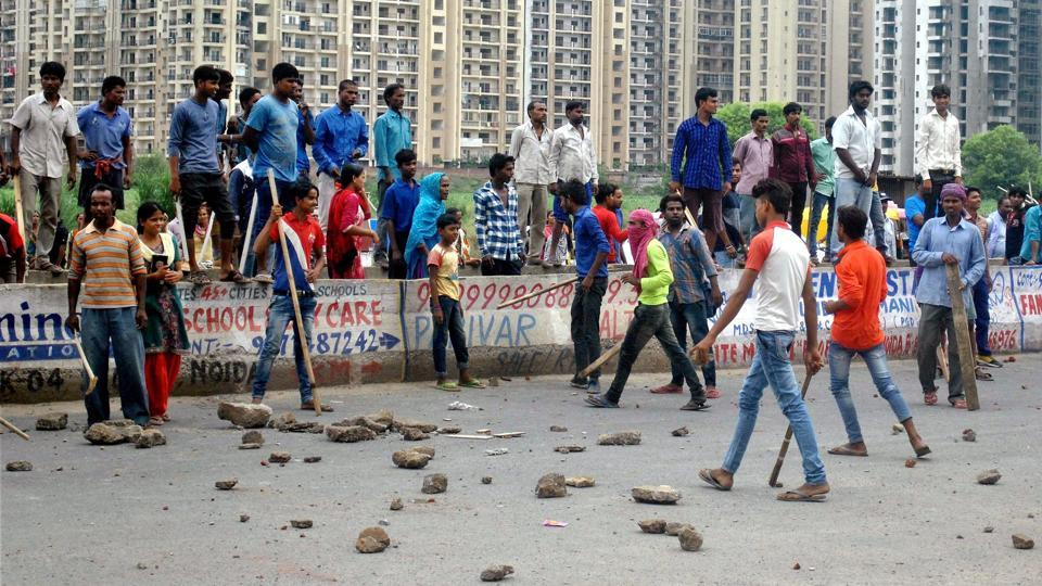 Local villagers gather at a housing society to protest after a domestic help was allegedly beaten by her employers on suspicion of theft in Noida. (PTI)