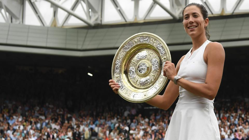 Spain's Garbine Muguruza holds up the Venus Rosewater Dish as she celebrates beating American Venus Williams to win the women's singles final at Wimbledon.